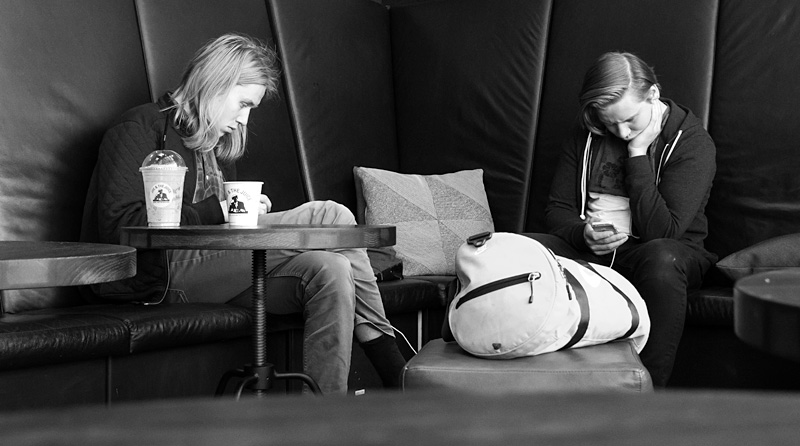 Grabbar med mobiltelefoner i soffa